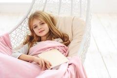 Niño alegre que se relaja en dormitorio con literatura Imagen de archivo libre de regalías