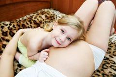 Niño alegre sobre una madre embarazada. Foto de archivo libre de regalías