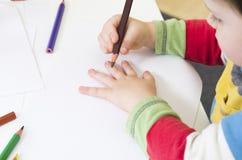 Niño alrededor para dibujar un esquema de su mano fotografía de archivo libre de regalías