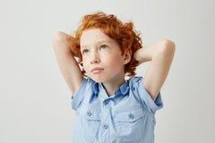 Niño apuesto del jengibre con las pecas que cruzan las manos detrás de la cabeza, mirando a un lado de sueño sobre la nueva video Imagenes de archivo