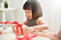 Niño asiático alegre que celebra con una caja de regalo fotografía de archivo libre de regalías