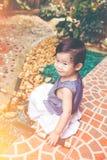 Niño asiático con el equipo que cultiva un huerto Al aire libre para los niños vin Imagenes de archivo