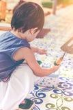 Niño asiático con el equipo que cultiva un huerto Al aire libre para los niños vin Fotos de archivo libres de regalías