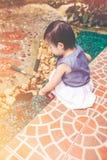 Niño asiático con el equipo que cultiva un huerto Al aire libre para los niños vin Imagen de archivo libre de regalías