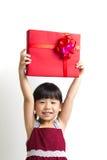Niño asiático con el rectángulo de regalo rojo Foto de archivo