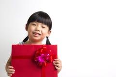 Niño asiático con el rectángulo de regalo rojo Imágenes de archivo libres de regalías
