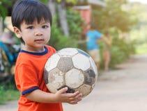 Niño asiático en el pueblo pobre que juega con el balón de fútbol Imagen de archivo libre de regalías