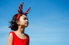Niño asiático en venda del reno Imagenes de archivo