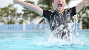 Niño asiático feliz que juega en piscina con la cara de la sonrisa