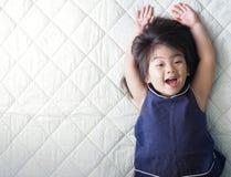 Niño asiático feliz que miente en cama, muchacha divertida del niño con el fondo blanco de la textura de la tela Foto de archivo libre de regalías