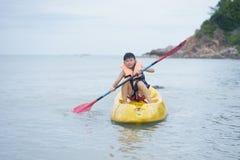 Niño asiático kayaking solamente en el chaleco de vida del mar que lleva imágenes de archivo libres de regalías