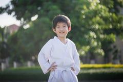 Niño asiático lindo en el kimono blanco durante karate del entrenamiento imagen de archivo