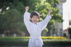 Niño asiático lindo en el kimono blanco durante karate del entrenamiento foto de archivo