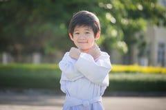 Niño asiático lindo en el kimono blanco durante karate del entrenamiento fotografía de archivo