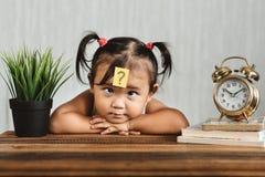 Niño asiático lookian lindo y confuso con el signo de interrogación en su frente fotos de archivo