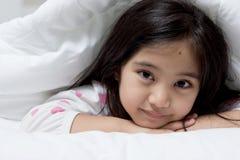 Niño asiático precioso que coloca en la cama imagen de archivo libre de regalías