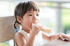 Niño asiático que come el pan foto de archivo libre de regalías
