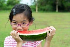 Niño asiático que come la sandía Foto de archivo