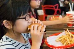 Niño asiático que come una hamburguesa y las patatas fritas Foto de archivo