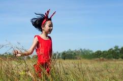 Niño asiático que corre en el campo Foto de archivo