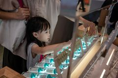 Niño asiático que elige los pendientes con su madre imagen de archivo