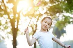 Niño asiático que juega el molino de viento al aire libre fotografía de archivo