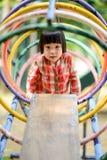 Niño asiático que juega en el parque de atracciones Imagenes de archivo