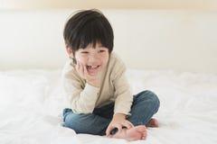Niño asiático que se sienta en la cama blanca imágenes de archivo libres de regalías