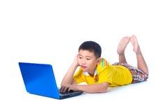 Niño asiático que usa un ordenador portátil, en el fondo blanco, aislado Foto de archivo