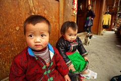 Niño asiático rústico 3 años, casa de madera del patio que se sienta. Imagenes de archivo