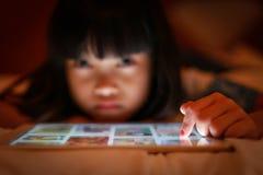 Niño asiático usando la pantalla de la tableta de Internet Fotos de archivo