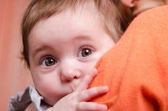 Niño asustado que oculta detrás del hombro de la mamá imágenes de archivo libres de regalías