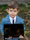 Niño atractivo contento, mostrando la tableta digital y sonriendo con la satisfacción y la actitud positiva imagenes de archivo