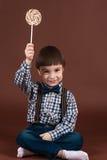 Niño atractivo que sostiene la piruleta disponible foto de archivo