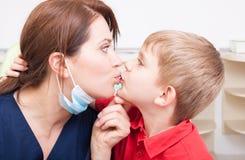 Niño atrevido e intrépido que besa a la mujer del dentista imágenes de archivo libres de regalías