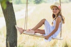 Niño bastante femenino que balancea en campo Imagen de archivo