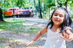 Niño bastante latino con un tren como fondo Imagen de archivo libre de regalías