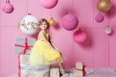 Niño bonito de la muchacha 6 años en un vestido amarillo El bebé en sitio de cuarzo de Rose adornó día de fiesta Foto de archivo libre de regalías