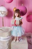 Niño bonito de la muchacha 4 años en un vestido azul Bebé que sostiene el regalo en sus manos El sitio de cuarzo de Rose adornó d Imágenes de archivo libres de regalías