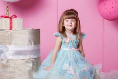 Niño bonito de la muchacha 4 años en un vestido azul El bebé en sitio de cuarzo de Rose adornó día de fiesta Imagenes de archivo