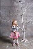 Niño bonito de la muchacha 3 años en un vestido rosado en sitio gris del día de fiesta con el árbol Imagen de archivo