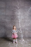Niño bonito de la muchacha 3 años en un vestido rosado en sitio gris del día de fiesta con el árbol Imagen de archivo libre de regalías