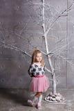 Niño bonito de la muchacha 3 años en un vestido rosado en sitio gris del día de fiesta con el árbol Foto de archivo