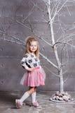 Niño bonito de la muchacha 3 años en un vestido rosado en sitio gris del día de fiesta con el árbol Fotos de archivo libres de regalías