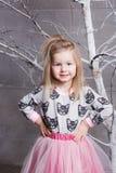 Niño bonito de la muchacha 3 años en un vestido rosado en sitio gris del día de fiesta con el árbol Imagenes de archivo