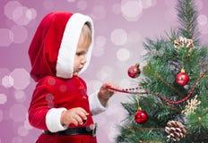 Niño bonito que adorna el árbol de navidad en brillante Imagenes de archivo