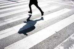 Niño borroso y su sombra en el paso de cebra Fotos de archivo