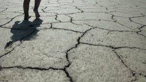 Niño a caminar descalzo en la tierra seca agrietada almacen de video