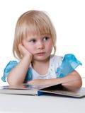 Niño cansado que mira el libro Foto de archivo libre de regalías