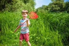 Niño caucásico adorable que juega con la cucharada-red en el prado en verano o día de primavera caliente y soleado fotografía de archivo libre de regalías
